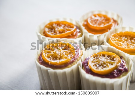 Vanilla Cupcakes With Orange Glaze and Candied Clementine in White Cupcake Wrappers on a White Wood Natural Background - stock photo