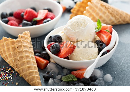Vanilla ice cream scoops with fresh berries - stock photo
