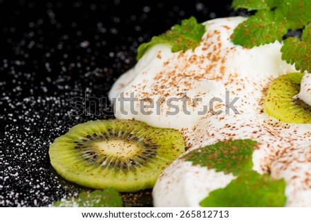 Vanilla ice cream with kiwi fruit and mint, on the black glass table - stock photo