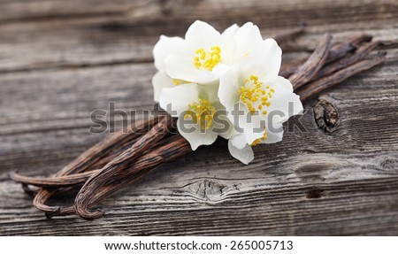 Vanilla pods with jasmine on a wooden background - stock photo