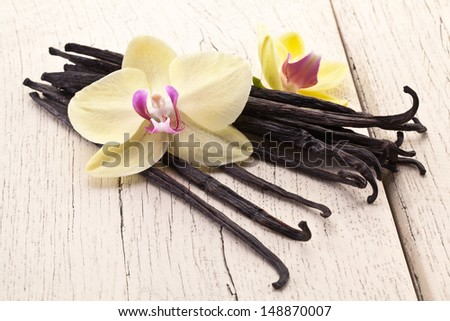 Vanilla sticks with a flower on a white wooden table. - stock photo