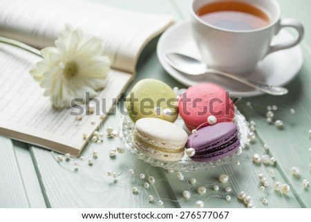 Vanilla, strawberry, pistachio and blueberry flavoured macaroons with pearls, flower and cup of tea on wooden background - stock photo