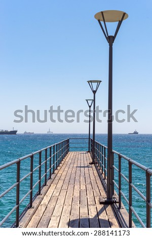 Vanishing pier with lamp and rails against with distant view on ships and oil platform on Mediterranean Sea horizon. Limassol, Cyprus.  - stock photo