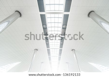 Vanishing roof of airport. Metal columns and white ceiling with glass windows. Symmetric architecture. Transparent roof of high building. Minimalistic design of construction. Public tourist place. - stock photo