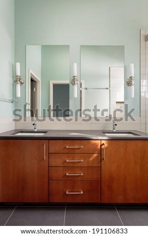 Vanity double sink and mirrors in modern bathroom/Vertical shot of a custom master bathroom vanity - stock photo