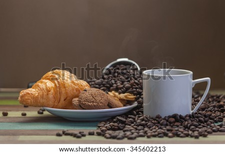 Vapor on coffee cup with cookies and beans background - stock photo