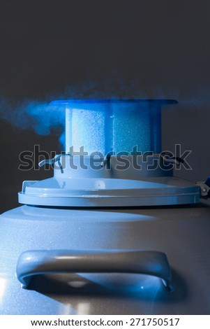 Vapour coming out of liquid nitrogen container, blue light - stock photo