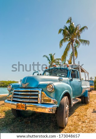 VARADERO, CUBA - APRIL 24: Old american car standing under palm tree backlighted by sun shown on 24 April 2008 in Varadero, Cuba - stock photo