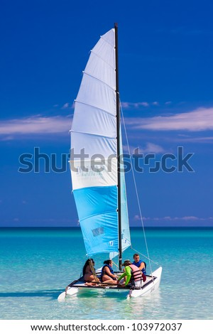 VARADERO,CUBA-MAY 27:Young tourists sailing in a catamaran May 27,2012 in Varadero.With over a million visitors per year,Varadero is the main destination for the growing cuban tourism industry - stock photo