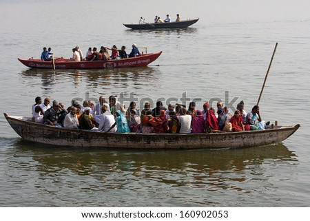 VARANASI, INDIA - DECEMBER 2: A lot of people sit on the crowded boats to cross the Ganges River on December 2, 2012 in Varanasi, India. The most holy river of India and Hindu culture. - stock photo