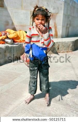 VARANASI, INDIA - 13 FEBRUARY: A poor girl with drum beggaring on the street of Varanasi. In the background sadhu sleeping on the pavement. Uttar Pradesh on February 13, 2008, Varanasi, India. - stock photo