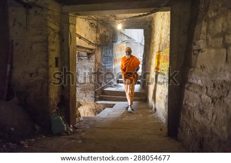 VARANASI, INDIA - 20 FEBRUARY 2015: A sadhu walks through a passage.  In Hinduism, a sadhu is a religious ascetic or holy person. - stock photo