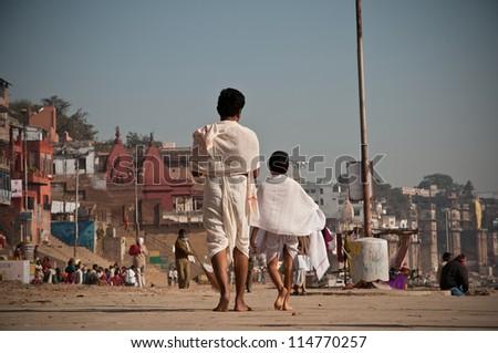 VARANASI, INDIA - FEBRUARY 19: Hindu pilgrims walk towards the temples on the auspicious Maha Shivaratri festival on February 19, 2012 at Dasashwamedh ghat in Varanasi, Uttar Pradesh, India. - stock photo