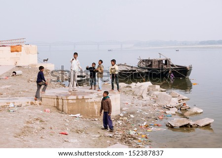 VARANASI, INDIA - JAN 1: Unidentified children play on the banks of the River Ganges, launching a kite on January 1, 2013. Varanasi had a population of 1,435,113. Approximately 138000 live in slums - stock photo