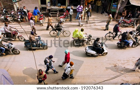 VARANASI, INDIA - JAN 4: View from above on the street traffic with crowd of people and vehicles on January 4, 2013 in indian city. Varanasi urban agglomeration has a population 1,5 million people  - stock photo