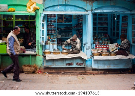 VARANASI, INDIA - JANUARY 2: Traditional street life with a sellers of small spices shops & passers-by people at morning on January 2, 2013. Varanasi urban agglomeration had a population of 1,435,113  - stock photo