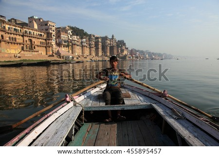 VARANASI, INDIA- MAR 12:Unidentified boatman rows his boat to ride visitors across the Ganges on March 12, 2016 in Varanasi, Uttar Pradesh, India.Varanasi is the most popular pilgrim place in India. - stock photo
