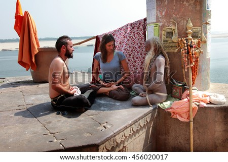 VARANASI, INDIA- MAR 03:Unidentified Hindu saint sits in a yoga position with foreign tourists on March 03, 2016 in Varanasi, Uttar Pradesh, India.Varanasi is the most popular pilgrim place in India. - stock photo