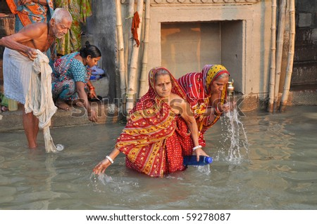 VARANASI, INDIA - 29 OCTOBER: An unidentified group of indian people wash themselves in the river Ganga on October 29, 2009 in Varanasi, India.  The holy ritual of washing is held every day. - stock photo