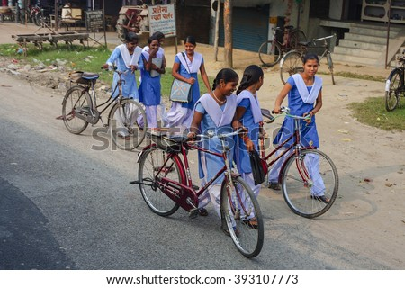 VARANASI, INDIA - OCTOBER 28: School girls going their homes from city to village, on bicycles, - popular indian transport, - October 28, Varanasi, India - stock photo