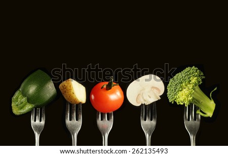 Variation of fresh vegetables on a black background, zucchini, potato, tomato, mushroom and broccoli - stock photo