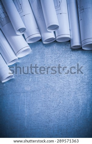 Variation of rolled up white construction plans on scratched silver-metal surface building and architecture concept. - stock photo