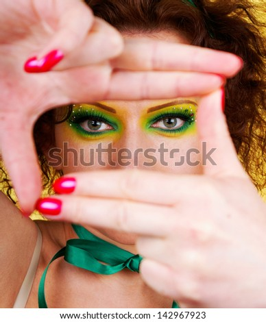 Variegated make-up girl, taking picture with imaginary camera, making frame with hands, selective focus - stock photo
