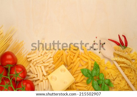 varieties of pasta, cheese and tomatoes on wooden board - stock photo