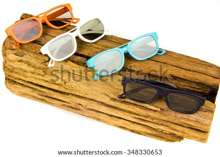 Varietry colored 3D glasses on wooden block isolated in white background - stock photo