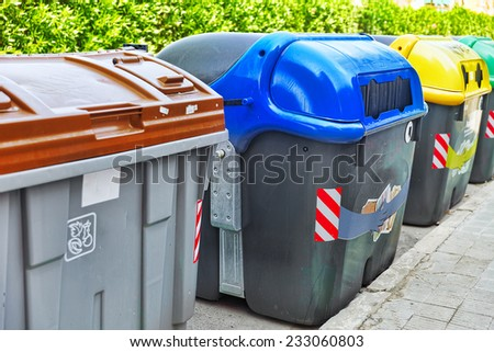 Variety dumpsters(recycling containers ) on a city street - stock photo