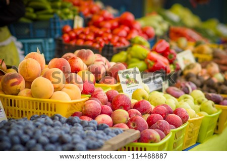 Variety of apples and peaches on city market - stock photo
