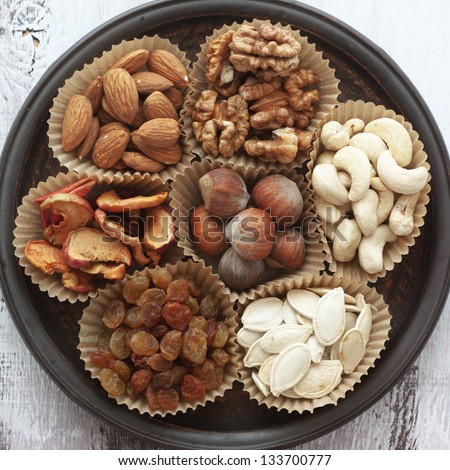 Variety of 7 assorted nuts and dried fruits - stock photo