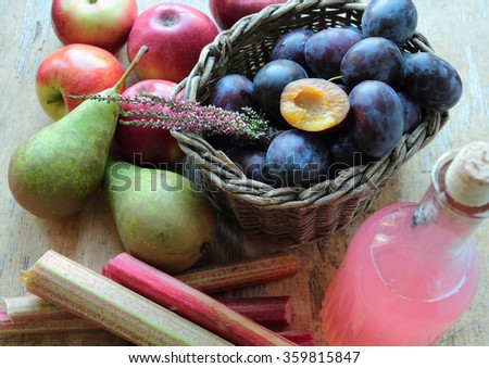 Variety of autumn fruits - apples, pears, plums and rhubarb with fresh juice in a glass bottle - stock photo