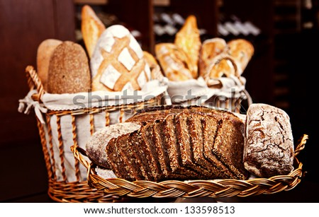 Variety of baked bread in baskets on black background - stock photo