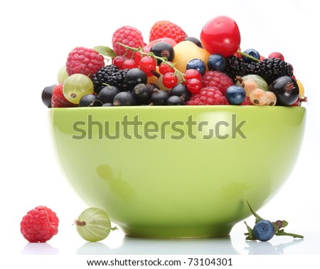 Variety of berries in a green bowl on white background. - stock photo