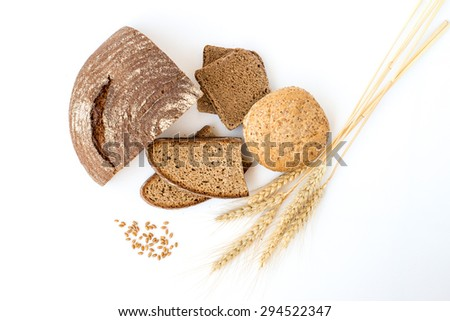 Variety of bread and stalks of wheat isolated on white - stock photo