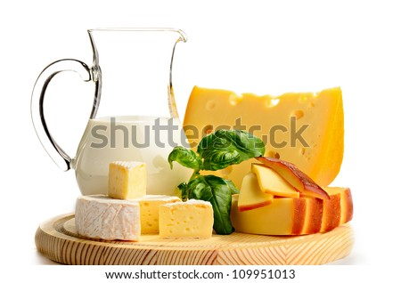 variety of cheeses with milk on wooden platter on white background - stock photo