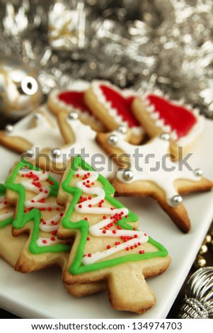 Variety of christmas cookies in a white plate with christmas tinsel in background - stock photo