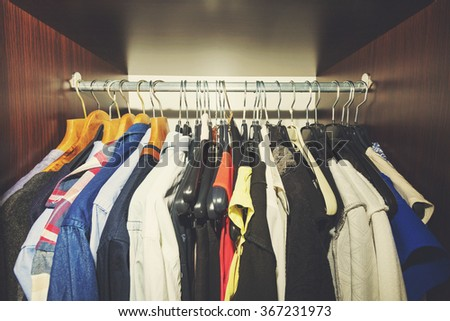 variety of clothes hanging in wooden wardrobe - stock photo