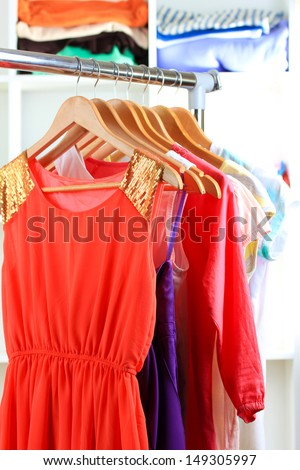 Variety of clothes on wooden hangers on shelves background - stock photo