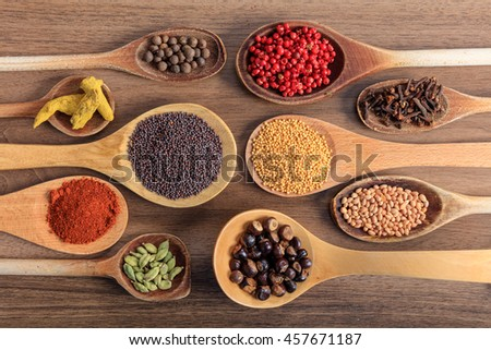 Variety of colorful spices, wooden surface - stock photo