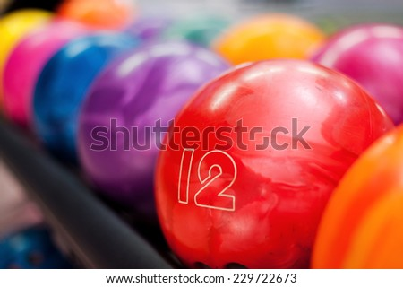 Variety of colors. Close-up of bright red bowling ball lying in the rows of other colorful balls  - stock photo