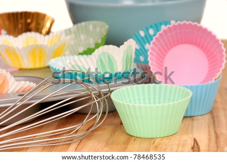 Variety of cupcake liners in different colors with a muffin pan and wire whisk - stock photo
