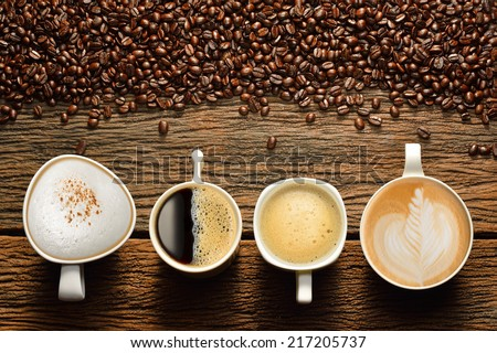 Variety of cups of coffee and coffee beans on old wooden table - stock photo