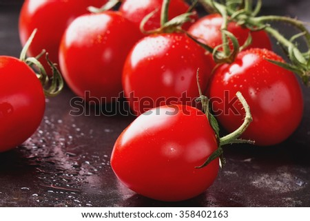 Variety of different tomatoes: red, orange, yellow and cherry on the cutting board and black metal tray - stock photo