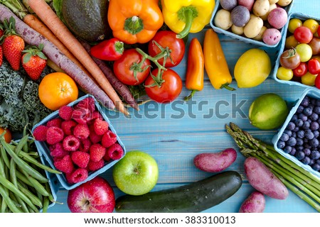 Variety of fresh raw organic fruits and vegetables in light blue containers sitting on bright blue wooden background - stock photo