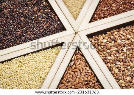 variety of gluten free grains (red and black quinoa, buckwheat, brown rive, amaranth and millet) in a wooden tray, focus on millet and rice - stock photo