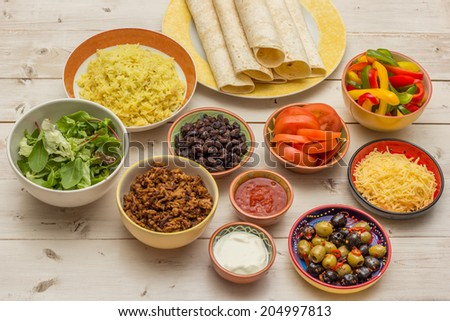Variety of ingredients to make mexican burritos with tortillas, rice, beans, ground beef, tomato, salsa, lettuce - stock photo