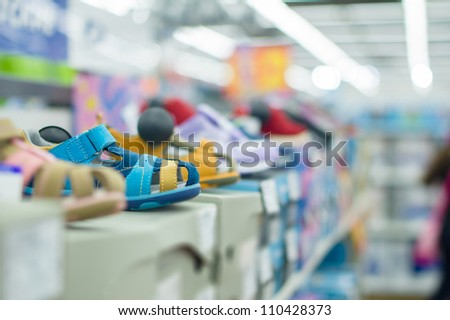 Variety of kid footwear on boxes in mall - stock photo