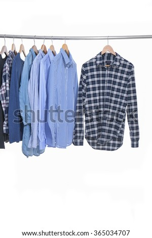 Variety of multicolored casual men's clothes shirts on hangers - stock photo